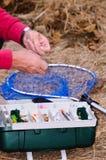 A fisherman binds fish hook. Royalty Free Stock Image