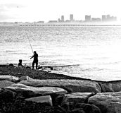 Fisherman in Black and white. There was a low fog around the city skyline of Boston as this fisherman waited for dinner stock photo