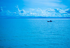 Fisherman and blue sky. Firsherman at work in the open water of Trad Thailand Stock Images