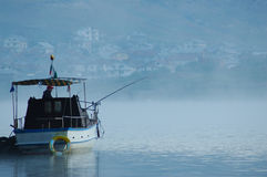 Fisherman in the boat. In the middle of Dospat  lake in Bulgaria Stock Photos