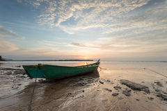 Fisherman boat at the beach during dramatic sunset Royalty Free Stock Images