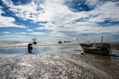 Fisherman and boat in blue sky Stock Photography