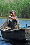 Fisherman in a boat in the Danube delta, Romania Royalty Free Stock Photography