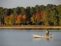 A fisherman on the boat. The first sights of autumn at the lake Royalty Free Stock Photo