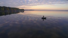 Fisherman in the boat. Fisherman in a boat at dawn on the lake stock video footage