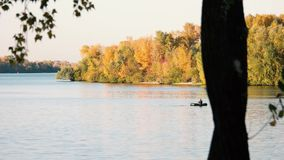 Fisherman in boat. River landscape with autumn trees stock video footage