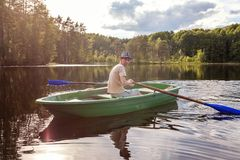 A fisherman in a boat. A fisherman is fishing in a boat on a beautiful lake Stock Photo