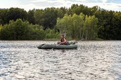 A fisherman in a boat. A fisherman is fishing in a boat on a beautiful lake Stock Photography