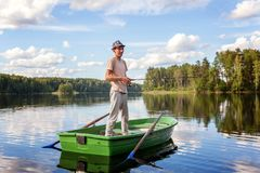 A fisherman in a boat. A fisherman is fishing in a boat on a beautiful lake Royalty Free Stock Photos