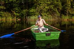 A fisherman in a boat. A fisherman is fishing in a boat on a beautiful lake Stock Images