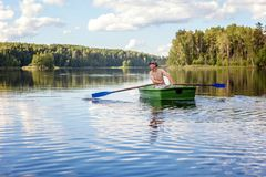 A fisherman in a boat. A fisherman is fishing in a boat on a beautiful lake Stock Image