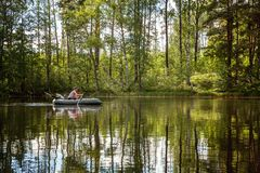 A fisherman in a boat. A fisherman is fishing in a boat on a beautiful lake Royalty Free Stock Photography
