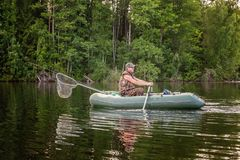 A fisherman in a boat. A fisherman is fishing in a boat on a beautiful lake Stock Photos