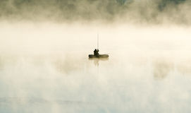 The fisherman by the boat in fog Royalty Free Stock Image