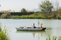 Fisherman on a boat. Fresh water lagoon in Estany de cullera. Valencia, Spain royalty free stock photography