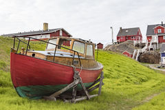 Fisherman boat in front of houses, Greenland Royalty Free Stock Photos