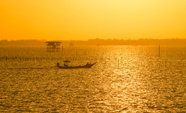 Fisherman boat with golden sunrise on the sea Stock Photos