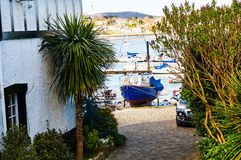 Fisherman boat harbour village. In Wales, UK, england cloudy sky and green hills Royalty Free Stock Images