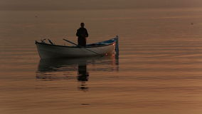 Fisherman on the boat. Fisherman on boat in Lake with very warm colors of sunset stock video