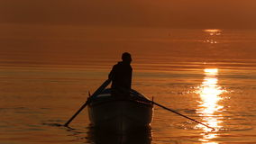 Fisherman on the boat. Fisherman on boat in Lake with very warm colors of sunset stock footage