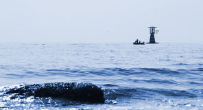 Fisherman on boat and lighthouse. In the middle of the sea Royalty Free Stock Image