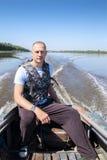Fisherman on  boat moves in  river Stock Image