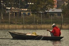 Fishing boat on Lake Feva in the background of the city royalty free stock image