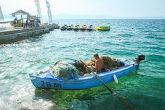 Fisherman in boat. NJIVICE, CROATIA - JUNE 24, 2017 : A fisherman in an anchored boat checking the fishing net with jet ski renting on the pier in the background royalty free stock photo