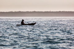 Fisherman in boat on ocean with big waves in Zanzibar Royalty Free Stock Photography