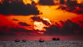 Fisherman on the boat over dramatic sunrise Stock Photos
