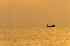 Fisherman on the boat over dramatic sunset Stock Images