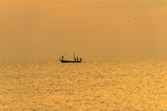 Fisherman on the boat over dramatic sunset Royalty Free Stock Image