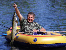 The fisherman in the boat with a pike Stock Photo