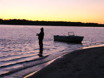 Fisherman with a boat on river. Evening time stock photos