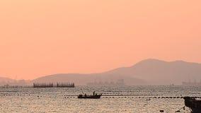 Fisherman boat run on sea with sunset sky stock video