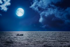 Fisherman boat sailing at night. Small fisherman boat sailing at night with full moon in the sky Stock Images