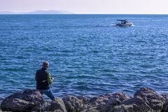 Fisherman and boat in the sea. Embankment in Istanbul royalty free stock photography