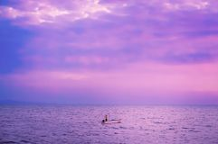 Fisherman with boat and sea with violet color filter effect. Fisherman with boat and sea and violet color filter effect royalty free stock photos