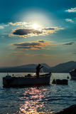 Fisherman and boat silhouette Stock Images