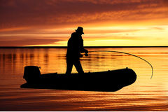 Fisherman on a boat at sunrise. Fisherman with a tackle  on a boat at sunrise Royalty Free Stock Images