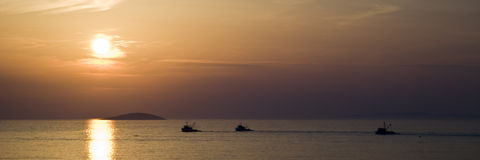 Fisherman boat sunset. Three Fisherman boats with island during sunset - panoramic format 1:3 - Croazia Royalty Free Stock Photos