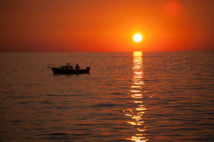 Fisherman in a boat during sunset Royalty Free Stock Photography