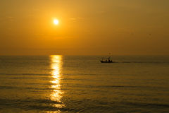 Fisherman on the boat at sunset time Royalty Free Stock Photography
