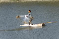 Fisherman on boat throwing stone stock image