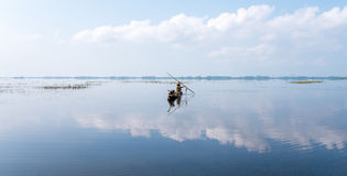 Fisherman on boat at wet land. Stock Photo