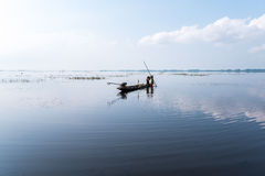 Fisherman on boat at wet land. Royalty Free Stock Photo