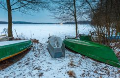 Fisherman boats on frozen lake shore. Winter landscape Royalty Free Stock Photos