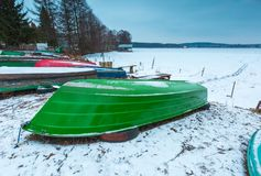 Fisherman boats on frozen lake shore. Winter landscape Royalty Free Stock Photography