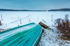Fisherman boats on frozen lake shore. Winter landscape Royalty Free Stock Images