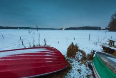 Fisherman boats on frozen lake shore. Winter landscape Stock Photos